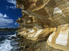Tasmania, Australia: Exposed sandstone rock patterns in the Painted Cliffs of Maria Island National Park, Darlington, Tasmania, Australia. Undercut by the Tasman Sea, the Painted Cliffs date back to the Permian and Triassic periods, 300-200 million years ago.