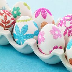 To make these pretty Easter eggs, punch shapes from double-sided adhesive, attach to eggs and roll them in glitter.