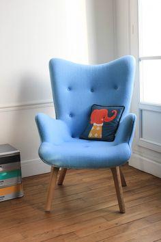 Un fauteuil cosy et rétro pour le coin salon de cet appartement. Plus de photos sur Côté Maison http://petitlien.fr/7viw