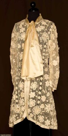 """Irish Crochet Coat, 1905-1910. 3/4 length, fitted, puff sleeve, many styles of flower blossoms, some 3-D, on wide crochet grid, edged in woven ivory silk tape, 3 large flat round buttons, satin neck sash above shallow V neckline, ivory cotton net lining, B 36"""", W 32"""", L 38"""". Augusta Auctions"""