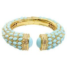 "Hinged bangle in turquoise with an Austrian crystal inlay.   Product: BangleConstruction Material: Metal alloy, resin and Austrian crystalsColor: Turquoise and goldFeatures:  HingedCrystal inlay Dimensions: 2.5"" DiameterCleaning and Care: Wipe clean with dry cloth"