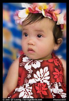 Baby girl in hawaiian dress wearing a flower lei on her head