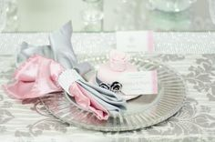 Beautiful place setting on our pink and silver table... serviette detail, miniature cakes and our lovely stationery.