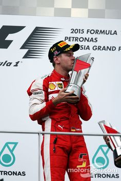 Malaysia Grand Prix winner Sebastian Vettel, Ferrari celebrates on the podium (Mar. 2015)