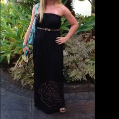 REDUCED Strapless  Maxi Dress You will love this amazing black Strapless maxi dress that  is perfect for summer. So cute and chic, this dress has a gold flower detail at bottom of the skirt and belted at the waist. You can wear this dress anywhere! Rhapsody Dresses Maxi