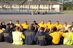 Seabees assigned to Naval Mobile Construction Battalion (NMCB) 11 lock arms and do sit-ups during a physical training on Naval Construction Battalion Center, Gulfport.