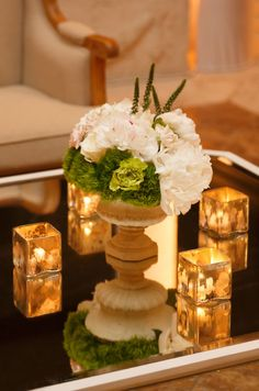 Sheer elegance is created with a floral urn arrangement /centerpiece surrounded by four gold votives atop a mirrored table.