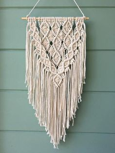 A modern macrame wall hanging made with 4 mm natural white cotton rope and a wooden dowel. This macrame piece is medium sized and a perfect fit for any space in your home. This macrame wall tapestry is inspired by my love of clean modern decor and boho style. It is the perfect piece to