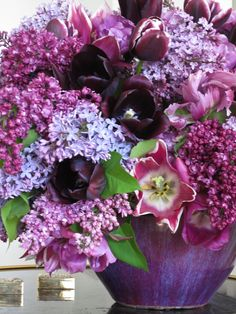 A variety of purple lilacs and tulips in an old bowl received as a gift from Bill Blass