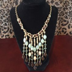 Dangle strand necklace NWOT. Bought this at a boutique. Beautiful gold dangle strand necklace with mint colored beads gold brown with a little strip of brown leather. Excellent to wear with a V-neck top or dress Jewelry Necklaces