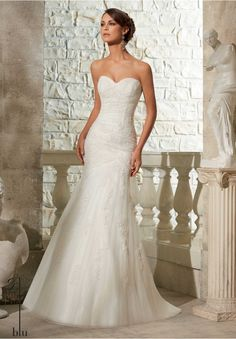 Wedding Gowns By Blu featuring Embroidered Appliques on Soft Net Sleek and elegant, this fit and flare wedding dress features asymmetrically draped Net accented with embroidered appliques. Complimented by a sweetheart neckline and covered button detail along the simple strapless back. Available in White, Ivory