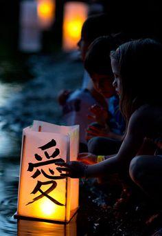 Boston, Massachusetts: Children set their lanterns afloat on Lake Hibiscus during the Japanese Bon festival at the Forest Hills cemetery Photograph: CJ Gunther/EPA
