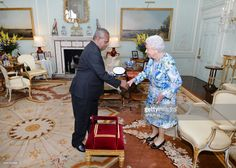 Queen Elizabeth II shakes hands with Sir Robert Dadae the Governor General of Papua New Guinea, and Lady Dadae during a private audience where he was knighted at Buckingham Palace on June 30 2017 in London, England..