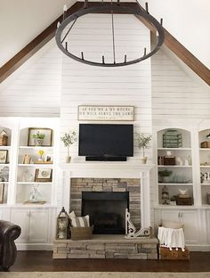 Beautiful Fireplace wall - As for Me & My House sign over fireplace, shiplap walls, built-in bookcases beautifully styled, dry stack stone fireplace, vaulted ceiling, wood beams, shiplap, trim, & cabinetry is Sherwin Williams Snowbound, wall color is SW Agreeable Gray, Capital Lighting Pearson Chandelier, dark hardwood floors