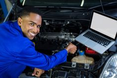 Mechanic examining car engine with help of laptop Free Photo