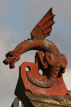 The Watcher - A red tile dragon sits on the roof of the Rye House pub beside the Lee and Stort Navigation in Hertfordshire.
