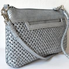 "Classic and sophisticated, this handbag gives you a modern look. Wear it to work or on your next job interview to give yourself professional style. Versatile enough to fit your personal and work life, this stylish look helps you transition from daytime to playtime.     Genuine snakeskin  2 exterior slip pocket , interior slip pocket, credit card slots and zip pocket  Converts from a cross body bag to a wristlet to a clutch, with 2 different removable handles  6"" tall x 10"" long"