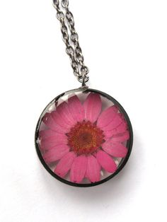 Encased in jewelers grade resin is a real dyed pink daisy! The copper pipe bezel is handmade by me and has a black finish. It would make a great gift
