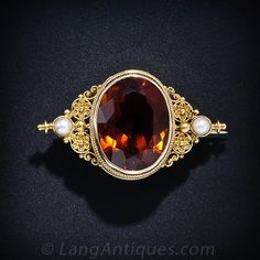 A deep golden amber Citrine is regally presented in a fine double rope bezel flanked by Etruscan revival style rosettes a lustrous pearl. 1 5/8 inches by 1 inch; circa 1890.