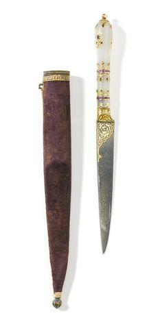 AN OTTOMAN JADE-HILTED SMALL DAGGER WITH SCABBARD, TURKEY, LATE 18TH CENTURY the blade of fine dark damascus steel damascened with gold arabesques at the forte, hilt composed of three sections joined by silver bands set with rubies and adorned with kundan floral details, original velvet covered sheath Quantity: 2 21cm. length. Estimate 18,000 — 25,000 GBP  30,137 - 41,858USD LOT SOLD. 32,500 GBP (54,415 USD)