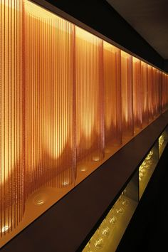 A thousand rose gold hued chains hang in a long undulating curtain along the side of the restaurant. This amazing lighting installation created a much needed sense of rhythm and movement to the dark space.