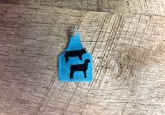 Blue sparkly ear tag pendant with black pig and lamb silhouette. Comes with rhinestone pinch bail. Repin to be entered to win one of four $50 gift certificates during our Five Year Anniversary Celebration in July 2014.