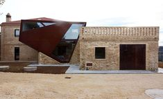 a corten and glass intervention between two historic masonry structures forms a new home that exhibits the contrast of material and construction throughout.