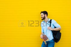 university students: handsome student with bakpack and a book on yellow background Stock Photo