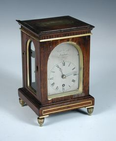 Full Details for Lot 835 - Cheffins William Cribb, London, a Regency rosewood and brass mounted timepiece of small proportions, the rectangular case with arched glazed panels to the four sides, countersunk brass handle to the top, the 7cm arched silvered dial signed above 'Willm Cribb London', Roman numerals, 4 pillar fusee movement with offset escapement, slightly arched plates, adjustable bob pendulum, all on four turned brass feet, now with a later made wall bracket h:19 w:12.50 cm