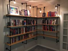 Lighted Pipe-Supported Shelves. DIY. Totally love this idea for my semi-finished basement. Would look awesome against those cement block walls!