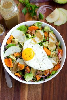 Fall Harvest Breakfast Salad with cinnamon roasted butternut squash and red onion, freshly diced apples, avocado slices, toasted walnuts, hemp seeds and an over easy egg.