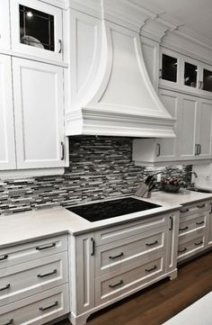 Gorgeous kitchen with crisp white cabinetry, marble countertops and black/grey tile backsplash