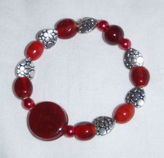 RED GLASS and SILVER HEARTS, BRACELET (Elasticated) 17cm - £3.50  1 x 20mm Flat Round Red Czech Glass Bead  4 x 6mm Pearl Red Glass Round Beads   5 x 10mm Red Czech Glass Beads   6 x 10mm x 10mm 'Pebble' Effect, Tibetan Silver Heart Beads