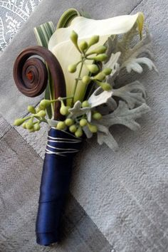 Fern curls..... this is the boutineer i was telling you about. but where the blue ribbon is, wrap completely in wire, then the green and whiteish stripped leaf, folded over behind the calla lily, was what i was thinking about doing with the blueish ribbon, but much wider, so the color stands our more.