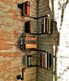 Plumbing pipe bookshelf. We can put this in the stairwell for the free library. It matches the banisters and a nice street to bar tie in.
