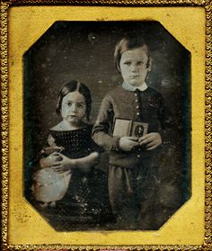 Brother and sister in mourning for their father. The girl with her doll.