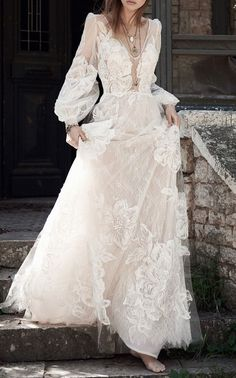 This Costarellos Bridal gown features a v neckline and bishop sleeves.