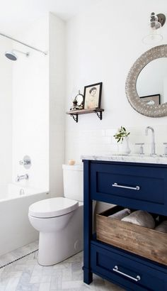 Vintage accessories in a modern bathroom with navy vanity.