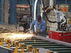 Soldador Fabricando una pieza metálica en el interior de la Planta de Soldado