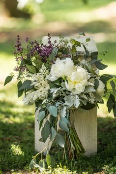 A Homegrown Minnesota Wedding: Bridal bouquet of purples, greens, and whites - peonies, astilbe, lilacs, wax flower, ranunculus, dusty miller, and seeded eucalyptus
