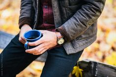 Man holding blue tin coffee cup while camping in the fall.  Isaiah & Taylor Photography for Stocksy United