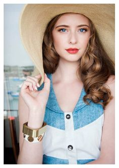 Ashlyn Pearce. The blue & white top does not suit her. The makeup, hat and gold bangles are gorgeous.