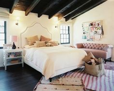 source: Lonny Magazine    Estee Stanley - Dark wood beams, Serena & Lily Pondicherry Bed With Nailheads, white nightstands, purple lamps, white & pink striped rug, Thomas O'Brien Bryant Sconces and pink tufted linen sofa. decorpad.com