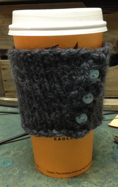 Knitted Coffee Cozy with pale blue accent buttons.