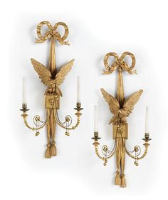 "<b>Pair of Regency-Style Carved Giltwood Two-Light Sconces,</b> mid-20th century, on tasseled ribbon backplates with bowknot crests, featuring eagles with chains and giltwood spherules on blocks with lion's heads, the scrolled candle arms decorated with medallions and terminating in engine-turned bronze candle cups and matching drip pans, electrified, h. 36"", w. 16"", d. 6-1/2""."