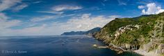 Italy -- The Cinque Terre Coastline by David.Kamm, via Flickr -- A wide view from an elevated hiking trail just south of the little hillside village of Riomaggiore. We stayed in this village and used it as a home base while exploring the five villages that dot the coastline in this area. At lower right is a very rocky 'beach' with a bunch of people enjoying the sun and water. Not super comfortable for lying around, but still fun to go swimming there.