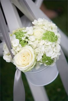 Fill small tin buckets with wedding flowers to decorate the ends of aisles or your table centres. This white bucket has been filled with ivory roses, white hydrangeas and small green flowers to add that touch of colour.