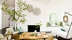 12 best warm neutral paint colors for your walls // white brick, fireplace, demijohn vases, raw wood coffee table, Danish armchairs, white leather chaise, hanging floor lamp, window seat // rustic Californian living rooms