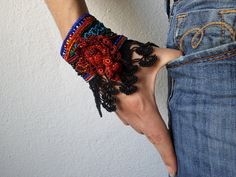 Beaded freeform crochet bracelet is created with black, green, red, indigo and gray fibers and seed beads, its decorated with a big burgundy