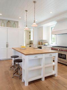 Beautiful white kitchen boasts a white kitchen island seating two industrial swivel counter stools in front of a butcher block countertop illuminated by two white glass light pendants hung from a shiplap ceiling.